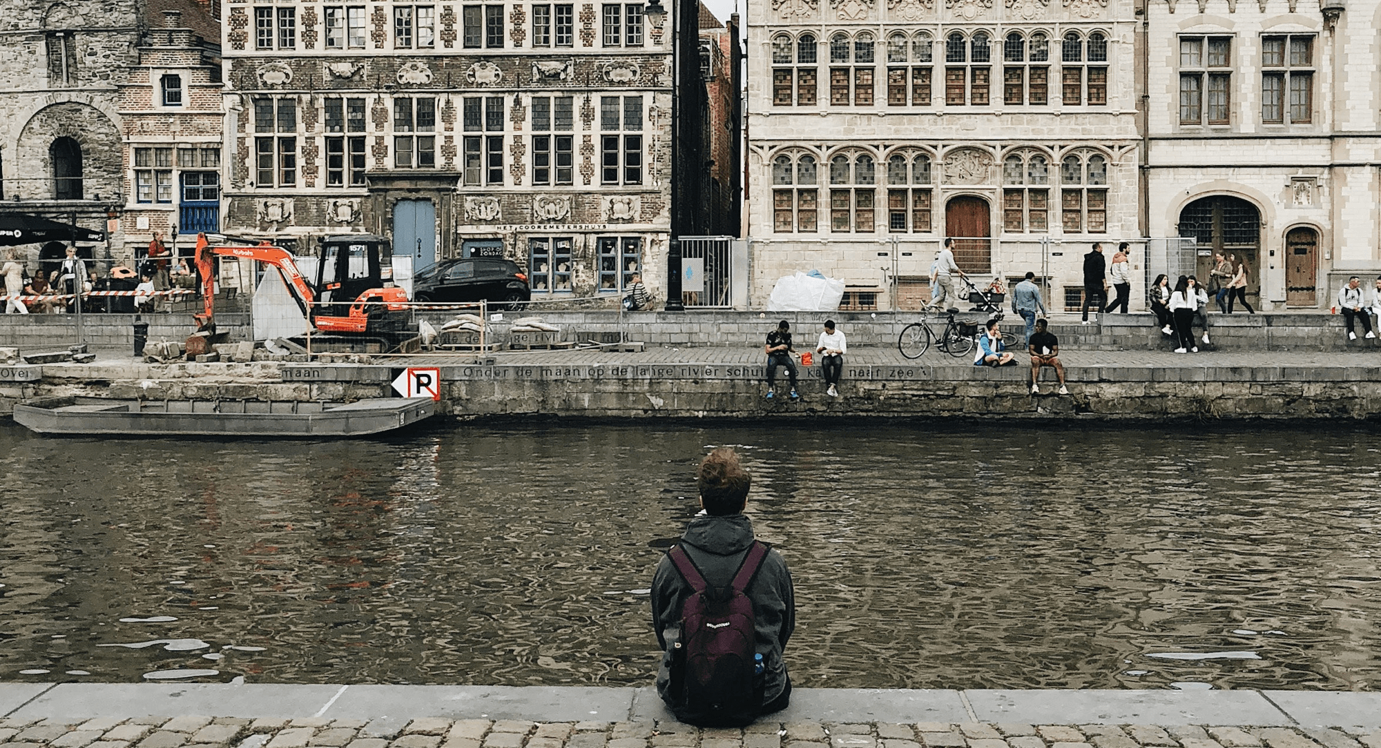 Boy sitting on the canal in Belgium